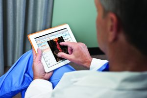 doctor looking at images on tablet